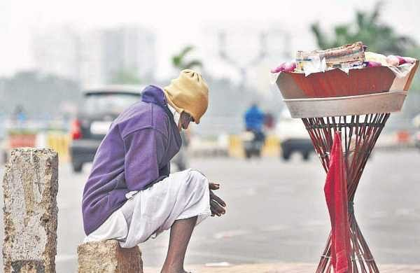 A roadside vendor keeping himself warm in the cool weather