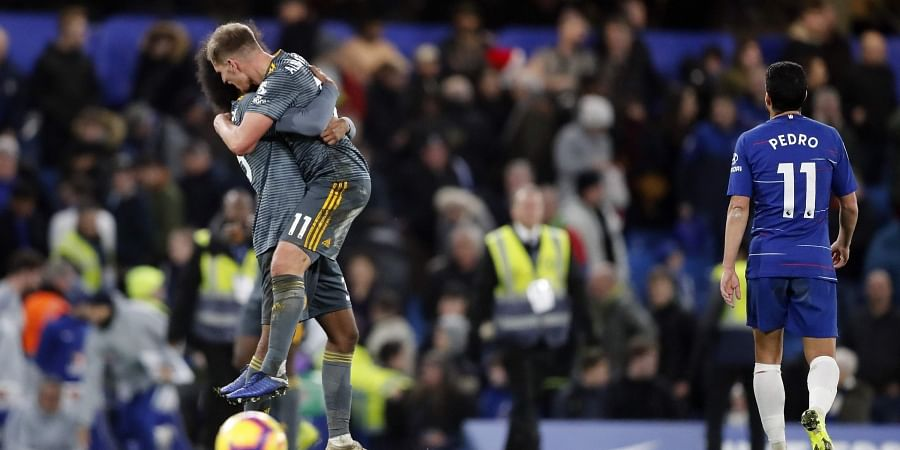 Leicester's Marc Albrighton and Leicester's Hamza Choudhury, left, celebrate as Chelsea's Pedro walks out in dejection after they won the English Premier League soccer match between Chelsea and Leicester City 0-1 at Stamford Bridge stadium in London. (Pho