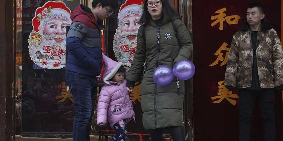 In this Saturday, Dec. 22, 2018, photo, a family walk past images of Santa Claus in Zhangjiakou in northern China's Hebei province. (Photo   AP)