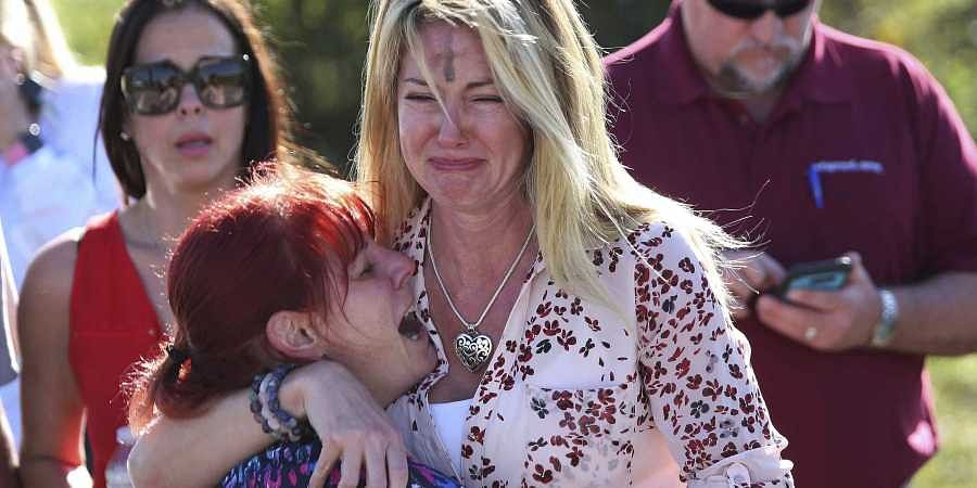 Parents wait for news of their loved ones after a mass shooting at Marjory Stoneman Douglas High School in Parkland, Fla., on Feb. 14, 2018. (Photo | AP)