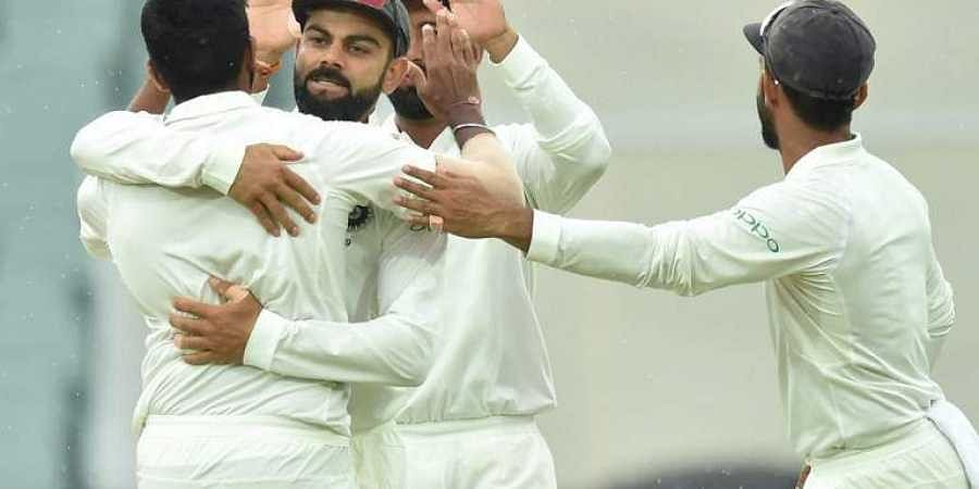 Indian captain Virat Kohli (2nd-L) congratulates bowler Jasprit Bumrah (L) after taking the wicket of Australia's batsman Mitchell Starc during day three of the first Test cricket match at the Adelaide Oval. (Photo | AFP)