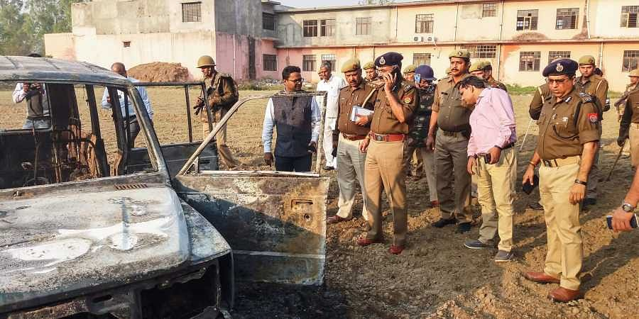 Cops inspect after several vehicles were set on fire by a mob during a protest over the alleged illegal slaughter of cattle in Bulandshahr Monday. (File photo | PTI)