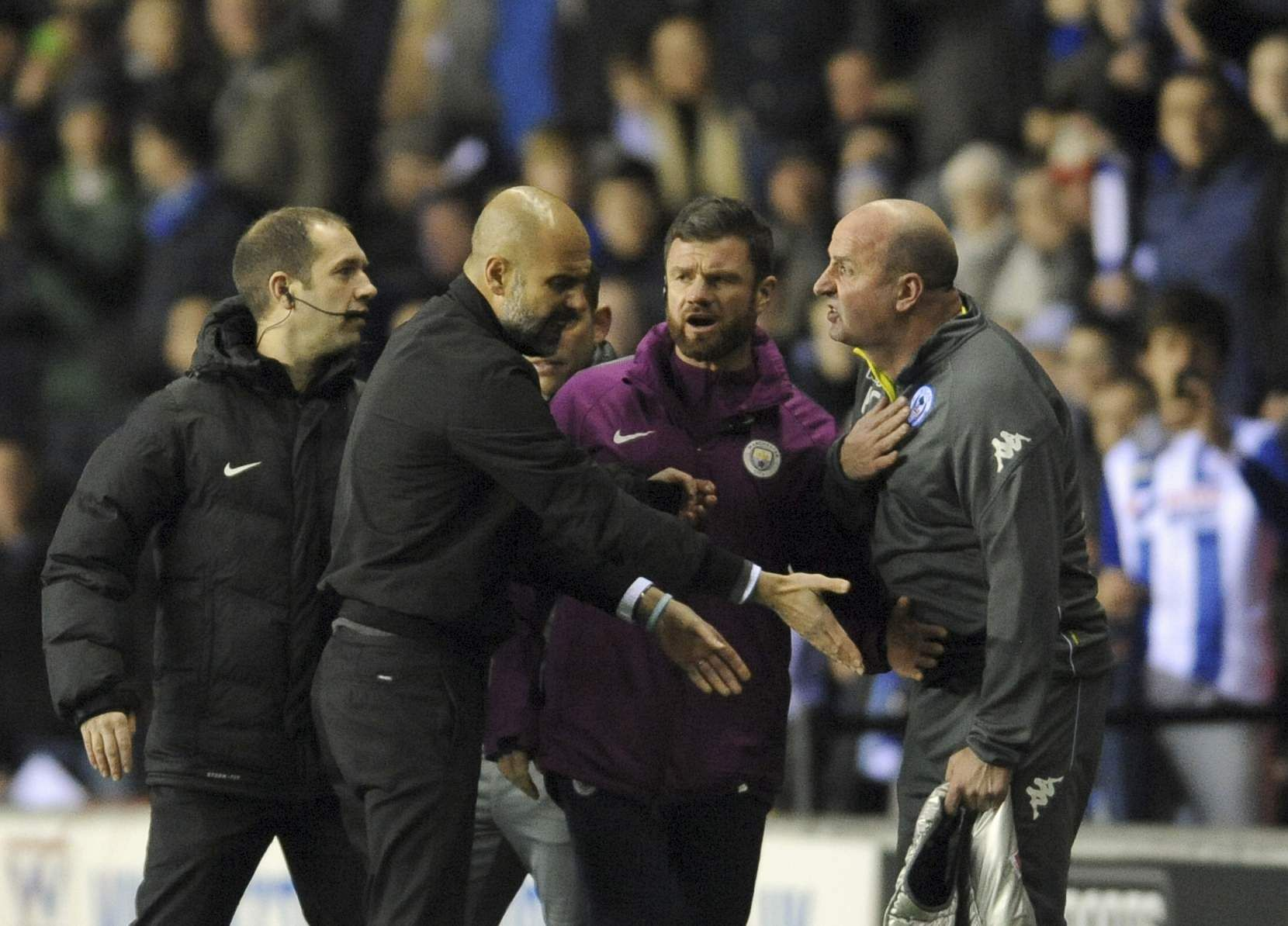 The scene turned even uglier as Manchester City manager Pep Guardiola, second from left, and Wigan manager Paul Cook, right, were involved in a major verbal confrontation. (AP)