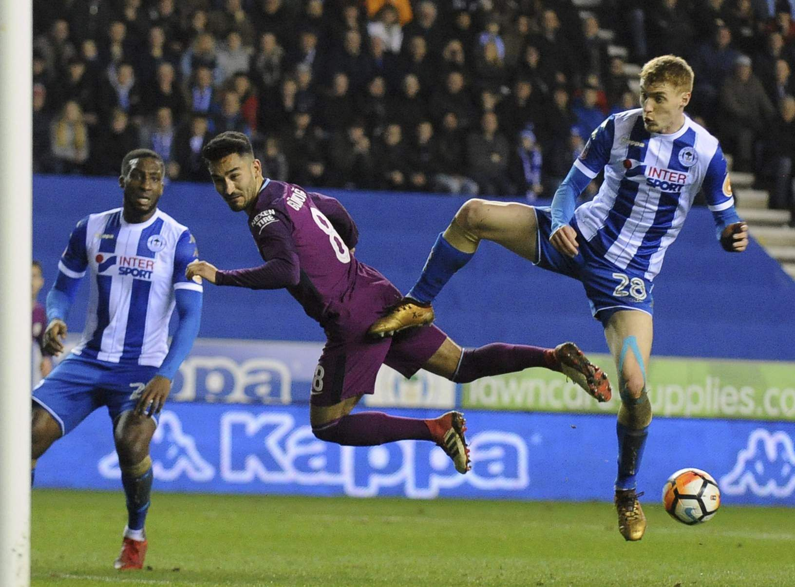 Wigan's Jay Fulton, right, duels for the ball with Manchester City's Ilkay Gundogan. (AP)