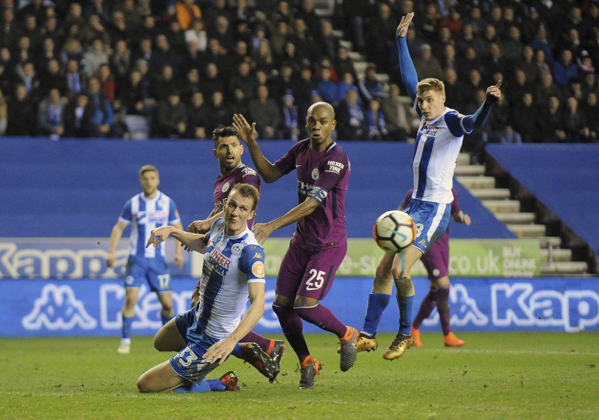 Manchester City's Fernandinho, center, duels for the ball with Wigan's Dan Burn, left. (AP)