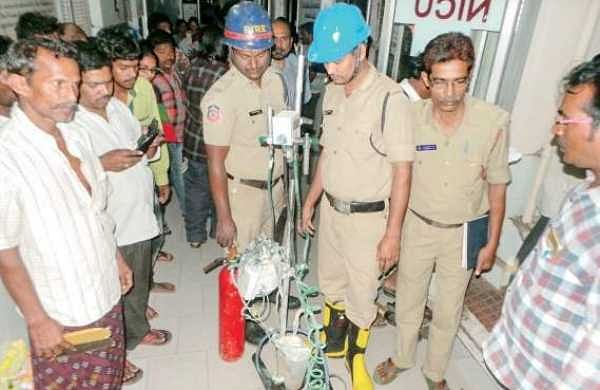 Fire personnel inspect the burnt CPAP machine at Kakinada Government General Hospital on Monday | Express