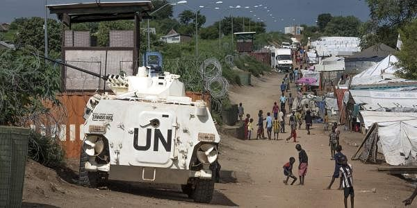 Some of the civilians sheltering in a United Nations base walk by an armoured vehicle and a watchtower manned by UN peacekeepers, in South Sudan's capital Juba. (File photo | AP)