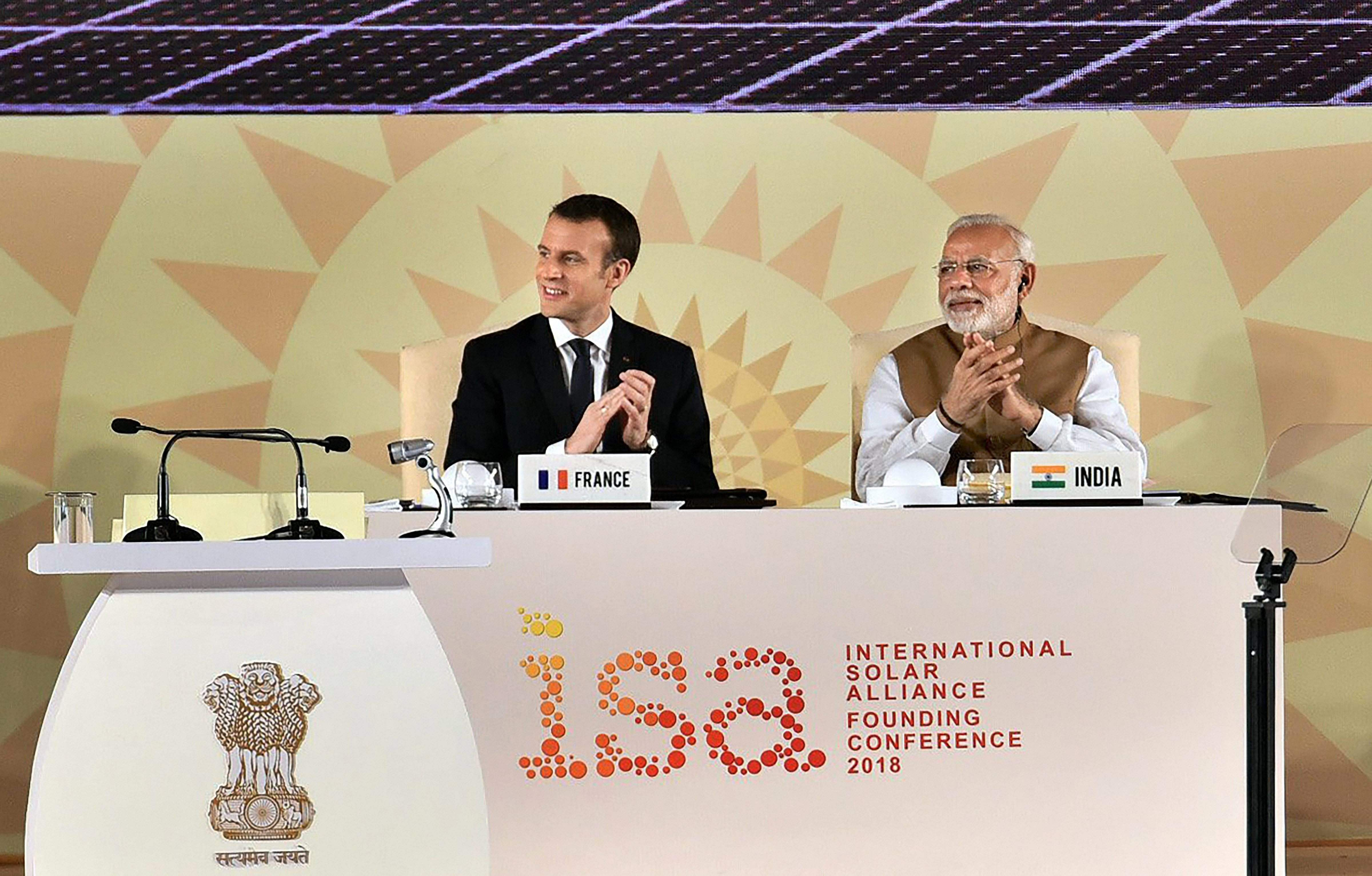 Macron takes dig at trump over paris climate agreement hails prime minister narendra modi and french president emmanuel macron clap at the international solar alliance founding conference in new delhi on sunday pti platinumwayz