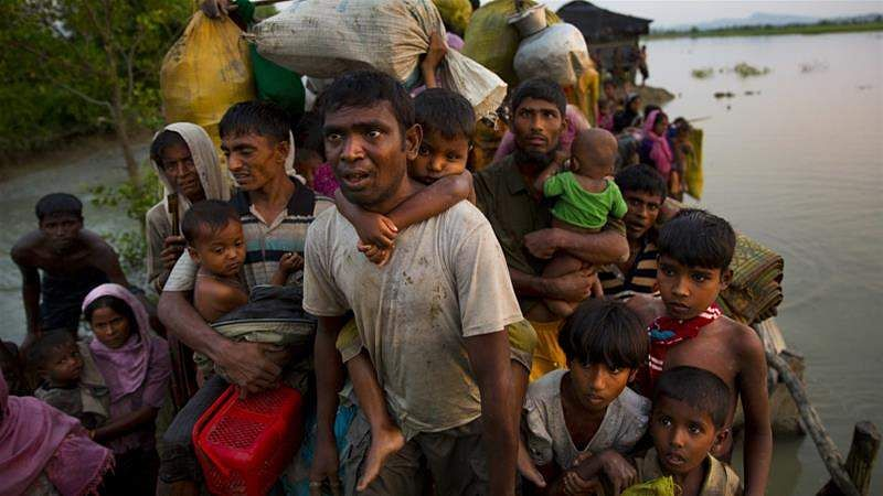 Rohingya Muslims carry their children and belongings after crossing the border from Myanmar into Bangladesh
