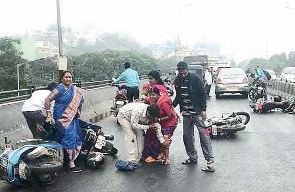 People picking themselves up after an accident at Telugu Talli flyover, in Hyderabad on Friday | Express