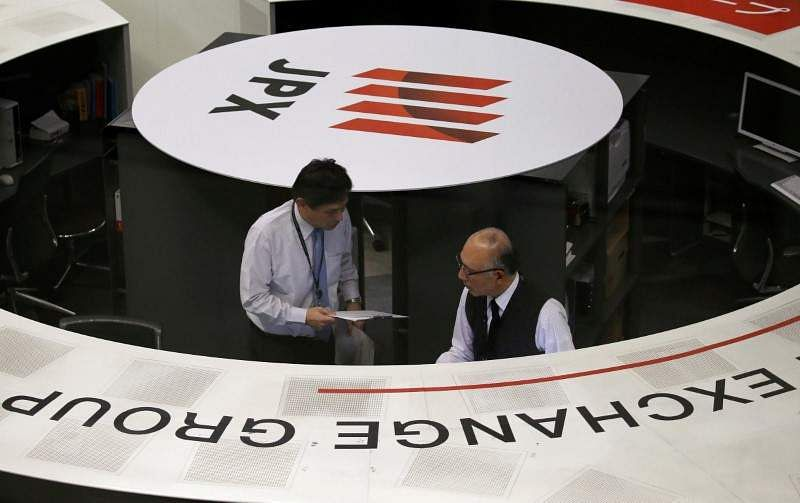 Employees of the Tokyo Stock Exchange work at the bourse in Tokyo Japan