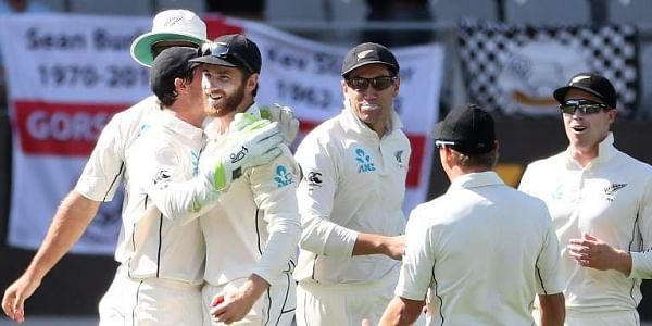 New Zealand's captain Kane Williamson (3rd L) is congratulated by teammates after taking a catch during the first day of the day-night Test cricket match between New Zealand and England at Eden Park in Auckland. | AFP