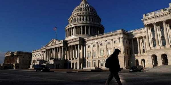 People walk by the U.S. Capitol building in Washington, U.S.  REUTERS