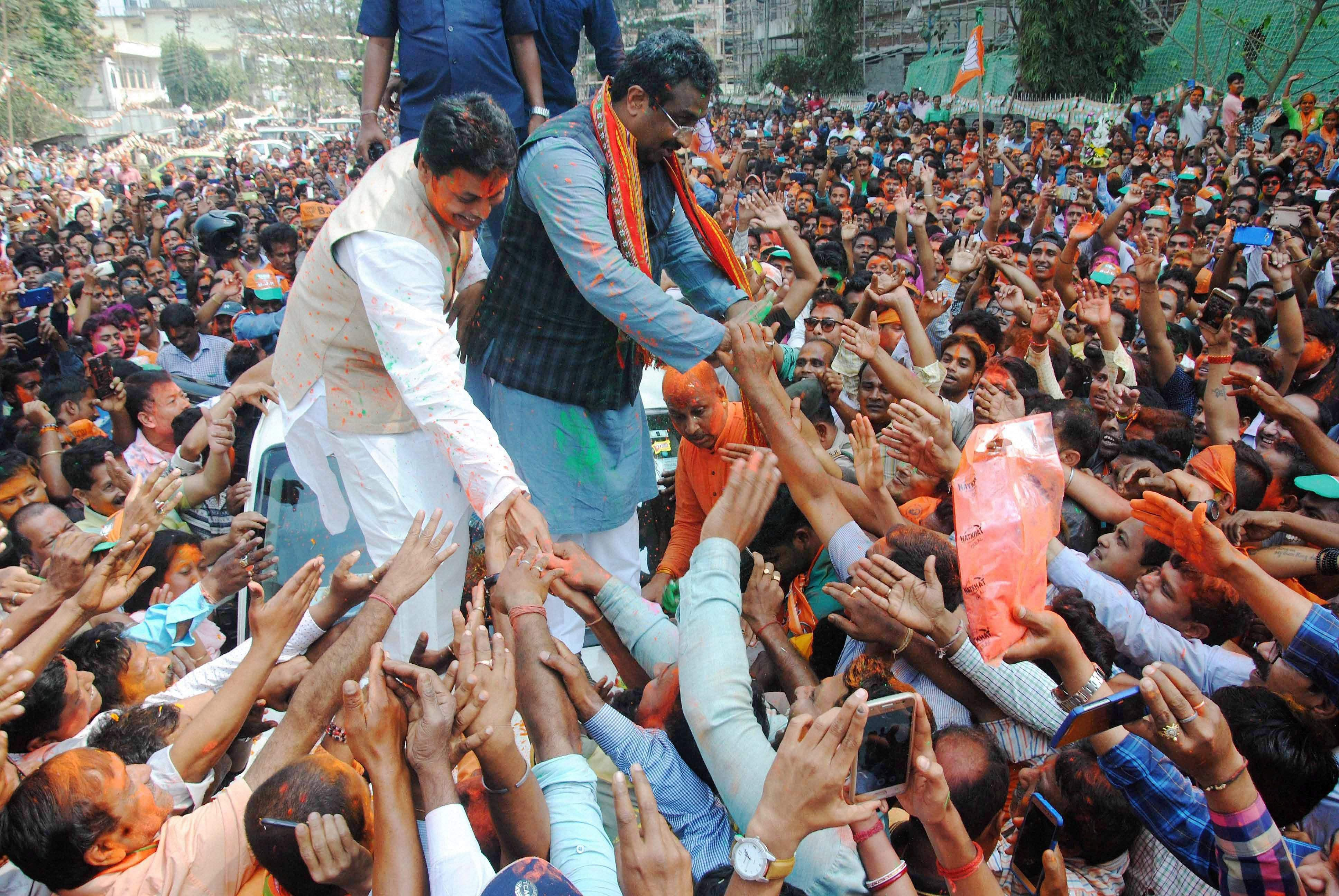 BJP National General Secretary Ram Madhav and Tripura BJP chief Biplab Kumar Deb display victory sign as they celebrate with supporters after party's victory in Tripura Assembly elections results in Agartala on Saturday. BJP's win marks an end to 25 years of CPI-M government rule in the state. (PTI)