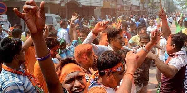 BJP supporters smear colors on each other to celebrate BJP's win which brought down 25 years of CPI-M government rule after Tripura Assembly election results were announced in Agartala. (PTI)