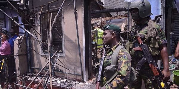 Sri Lanka's security forces stand near a vandalized building in Digana, a suburb of Kandy, Sri Lanka. | AP