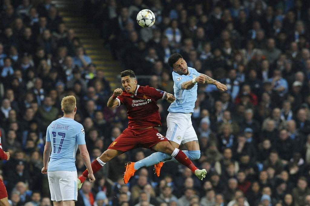 Liverpool's Roberto Firmino, centre, competes for the ball with Manchester City's Kyle Walker. (AP)