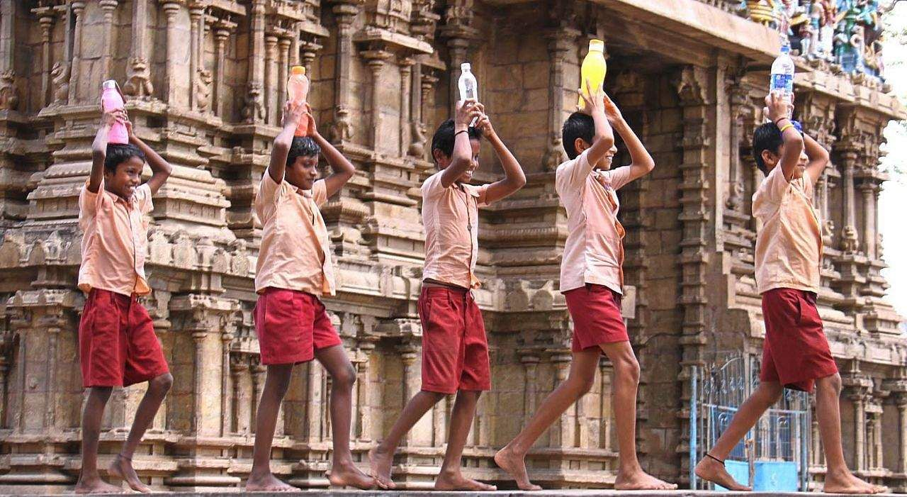 Caption: School students after getting few bottles of water are seen on a jolly run, in Alagarkovil, near Madurai,/express photo k.k.sundar