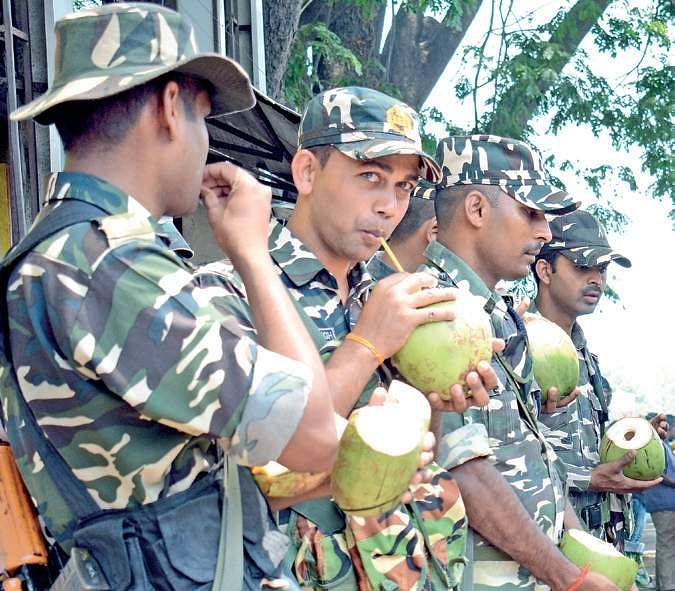 Sashastra Seema Bal personnel on election duty sip tender coconuts to beat the heat at Majestic in Bengaluru on Saturday | Shriram B N
