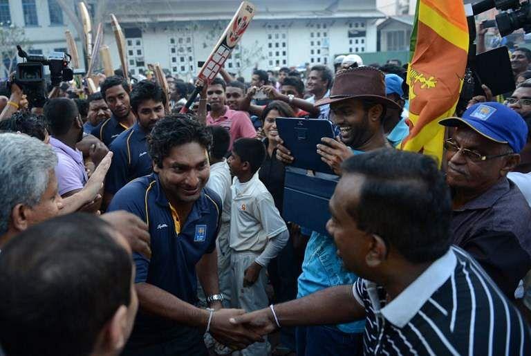 Sri Lankan Sports Minister Mahindananda Aluthgamage (R) shakes hands with Sri Lankan Cricketer Kumar Sangakkara. | File AFP