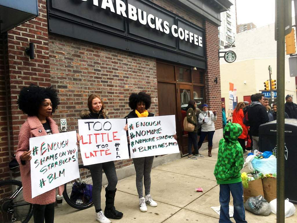Protesters gather outside a Starbucks in Philadelphia, Sunday, April 15, 2018, where two black men were arrested Thursday after Starbucks employees called police to say the men were trespassing. | AP