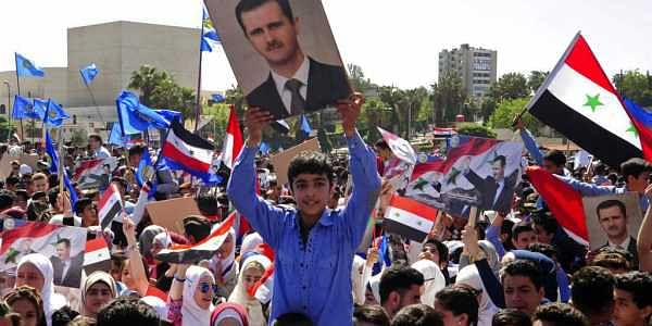 In this photo released by the Syrian official news agency SANA, protesters wave flags and portraits of President Bashar Assad, as they march during a demonstration to show solidarity with the Syrian armed forces, at Omayyad Square, in Damascus, Syria. | AP
