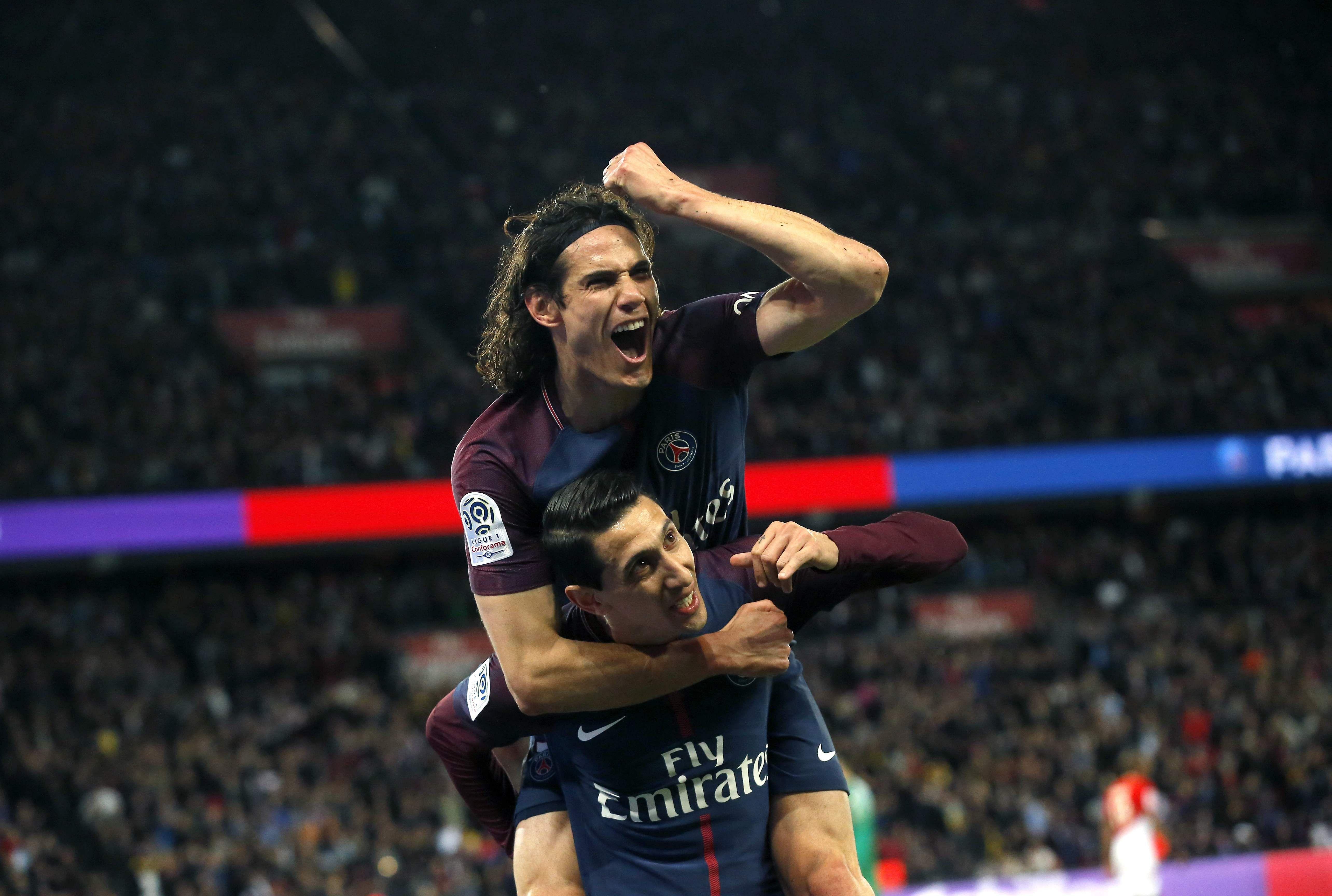 Paris Saint Germain's Angel Di Maria, down, celebrates with Edinson Cavani after scoring his side's third goal against Monaco. (AP)