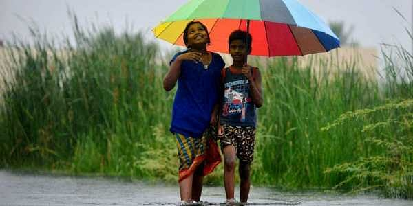(Image for representation only) 'Rainbow shade'- Two siblings brave the rains under an umbrella near Dandeeswarar Nagar, Velachery, Chennai. (EPS | Sunish P Surendran)