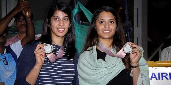 Squash players Joshna Chinappa and Dipika Pallikal Karthik display their Commonwealth medals on their arrival at the Chennai airport on Monday.   PTI