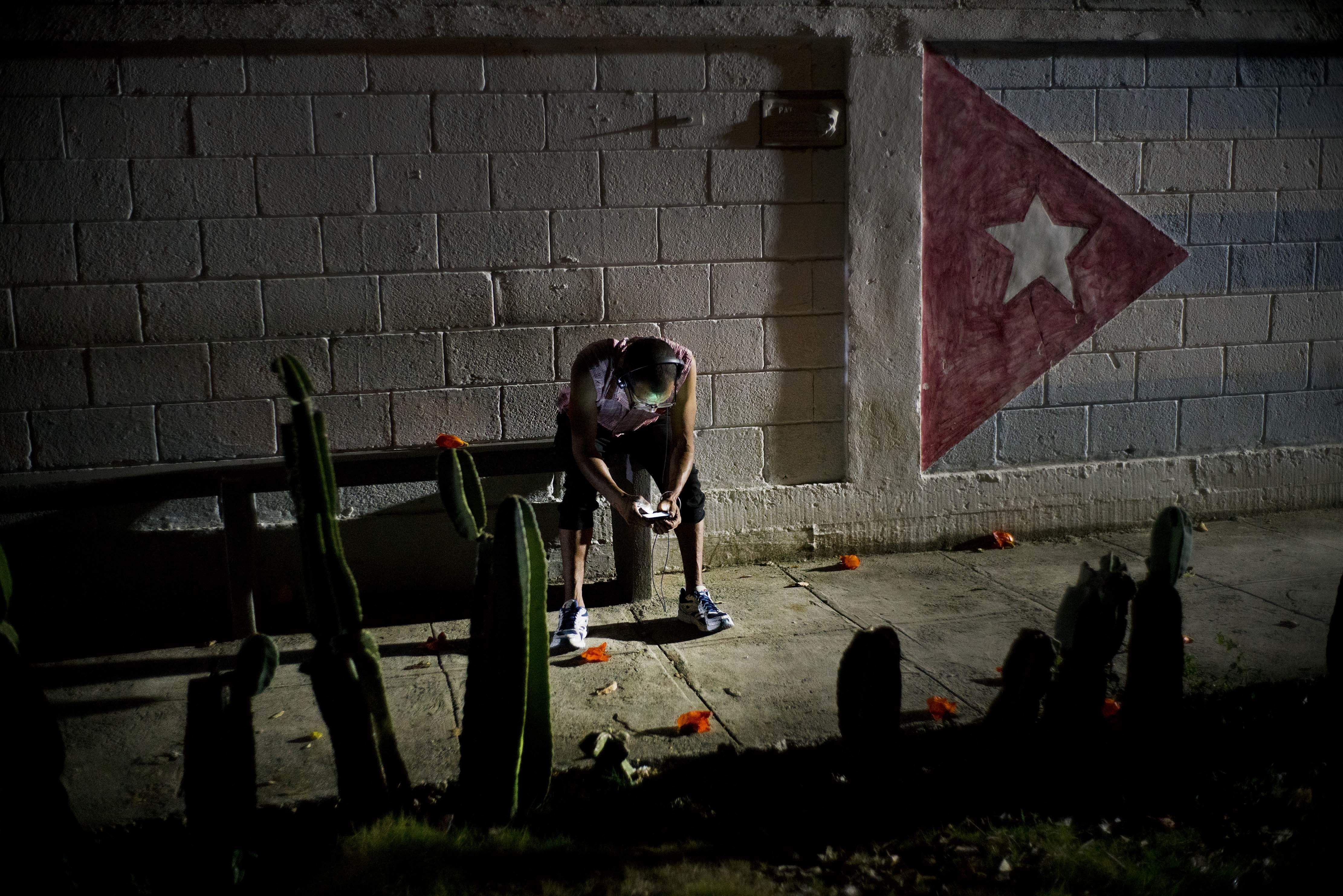 In this April 14, 2018 photo, Lazaro Rodriguez, 42, connects his cell phone at a public internet hot spot at night in Havana, Cuba.   AP