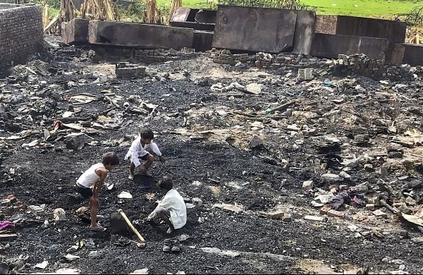 Children searching for their belongings in the charred debris of their homes a week after a Rohingya camp caught fire in Sarita Vihar in New Delhi. | PTI