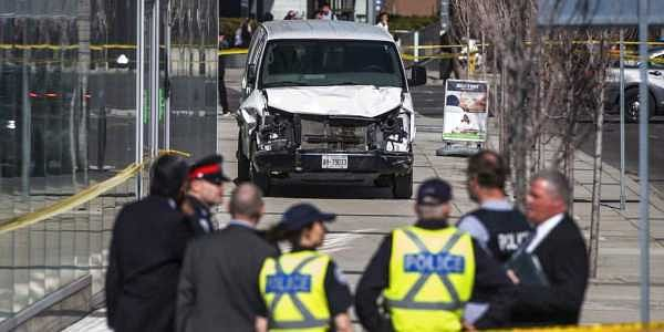 Police are seen near a damaged van after a van mounted a sidewalk crashing into pedestrians in Toronto. | AP