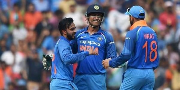 Indian wicket keeper Mahendra Singh Dhoni (C) celebrates with Kedar Jadhav (L) and captain Virat Kohli after the wicket. | File AFP