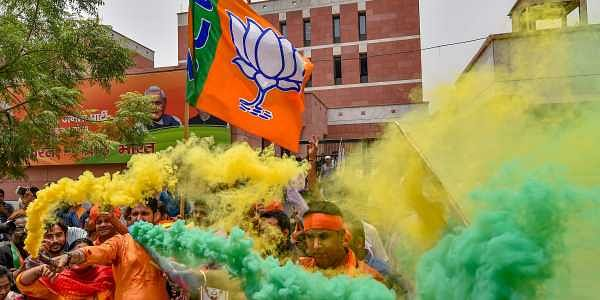 BJP workers celebrate the party's lead during counting of votes for Karnataka Assembly elections at the party headquarters in New Delhi on Tuesday. | PTI