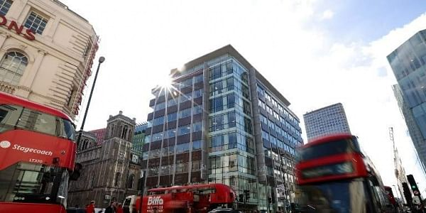 Traffic, including red London busses, passes the shared building which houses the offices of Cambridge Analytica in central London. | AFP