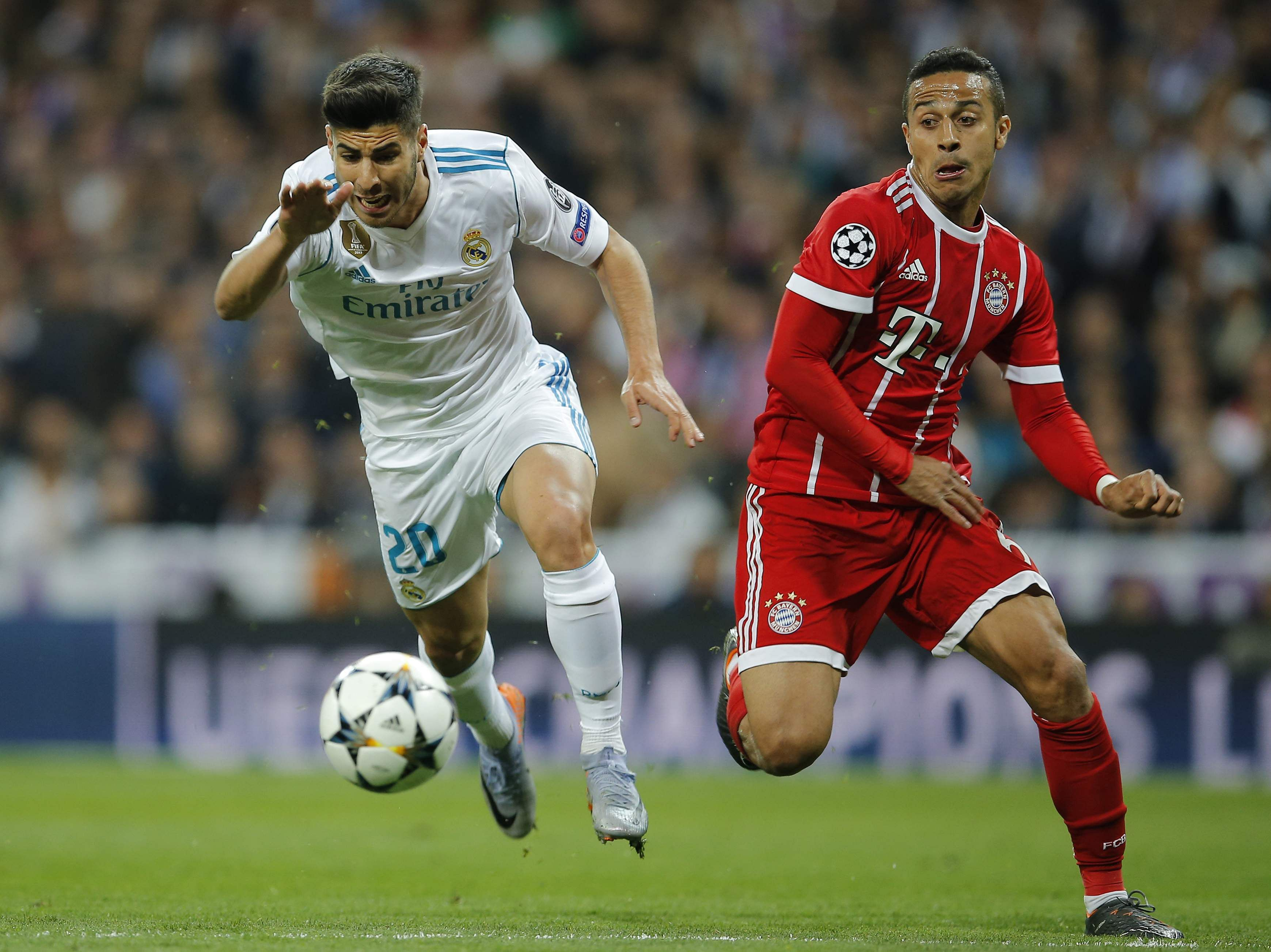 Real Madrid's Marco Asensio, left, and Bayern's Thiago challenge for the ball during the Champions League semifinal second leg match between Real Madrid and FC Bayern Munich at the Santiago Bernabeu stadium in Madrid. (AP)
