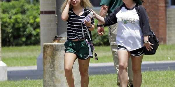 A student, left, reacts after retrieving her belongings inside Santa Fe High School in Santa Fe, Texas. | AP