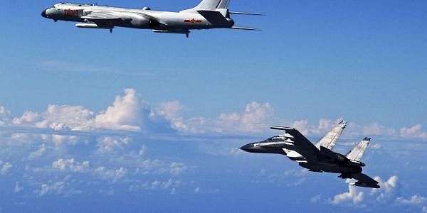 A Chinese People's Liberation Army Air Force Su-30 fighter, right, flies along with a H-6K bomber as they take part in a drill near the East China Sea. (File Photo | AP)