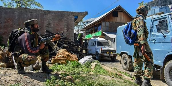 Security personnel stand guard during an encounter between security forces and militants at Drabgam in Pulwama District of South Kashmir on Monday. | PTI