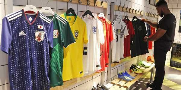 c7f274ed428 A customer looks at different national football team jerseys that are on  display at a shop in London