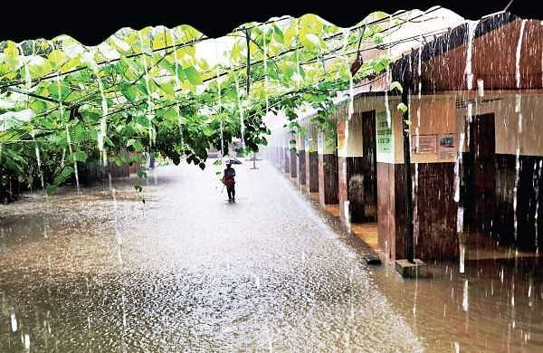 A scene from the waterlogged SRV School at South Junction, with students wading through the torrent to get back home on Thursday. Following the widespread disruption caused by heavy rain, the district administration declared a holiday for educational insitutions in the district on Friday | Melton Antony