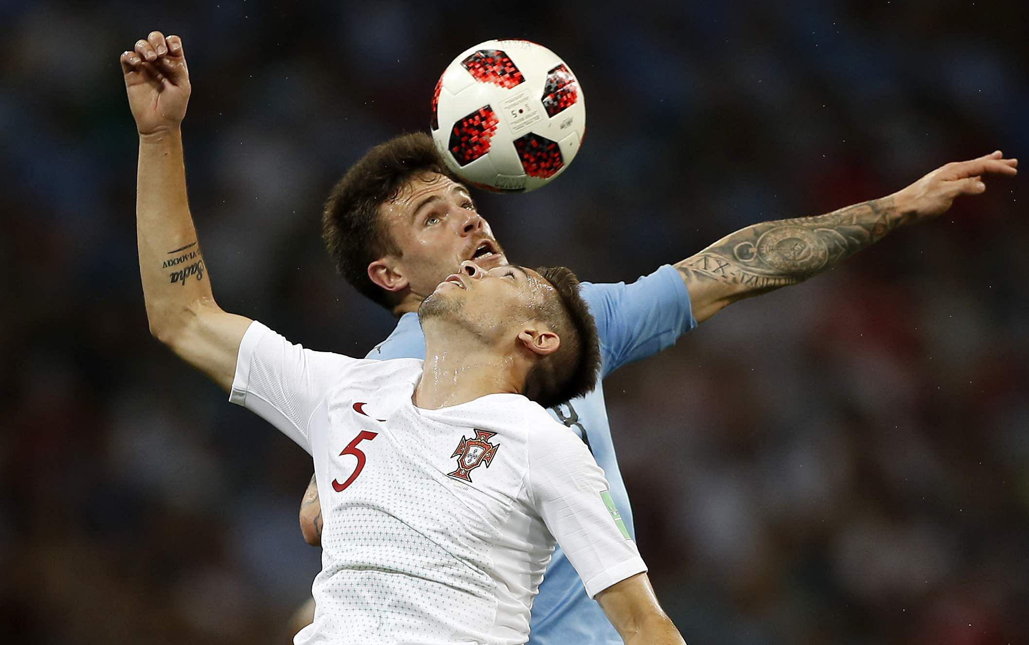Portugal's Raphael Guerreiro and Uruguay's Nahitan Nandez, top, challenge for the ball. (Photo | AP)