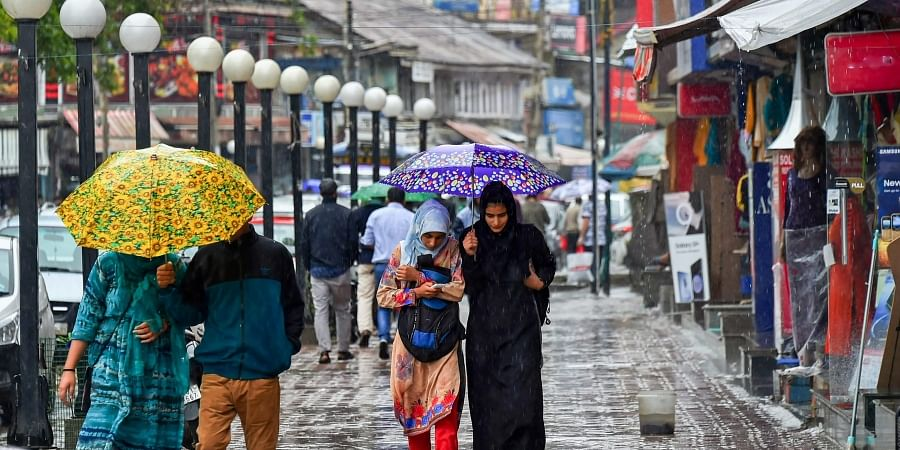 Pedestrians walk with umbrellas during heavy rains in Srinagar on Friday June 29 2018. Heavy rains lashed several parts of the Valley including the state's summer capital today even as the authorities advised people residing near streams in south Kashmir