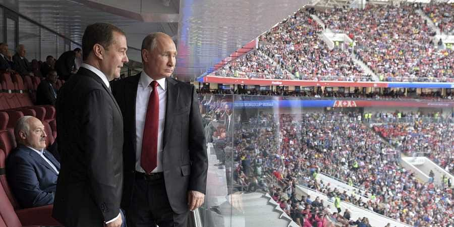 Russian President Vladimir Putin (R) and Russian Prime Minister Dmitry Medvedev look at the field during the opening match of FIFA World Cup 2018 between Russia and Saudi Arabia. (File Photo | AP)