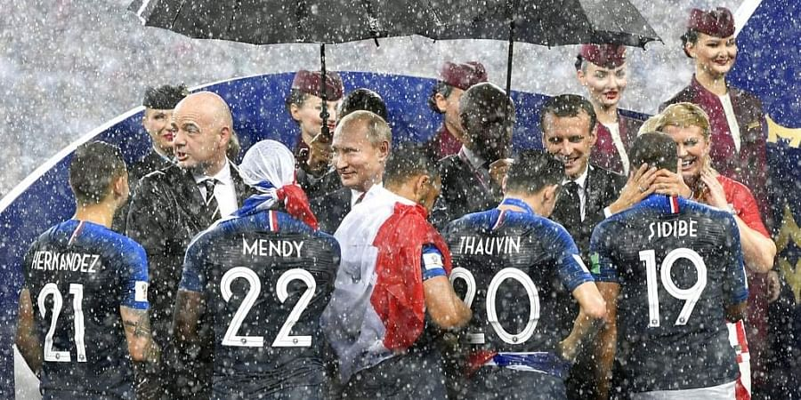 FIFA President Gianni Infantino, Russian President Vladimir Putin, French President Emmanuel Macron and Croatian President Kolinda Grabar-Kitarovic, from left, stand in the puring rain as they congratulate the French players after France won 4-2 in the final match between France and Croatia at the 2018 soccer World Cup in the Luzhniki Stadium in Moscow, Russia. (Photo | AP)