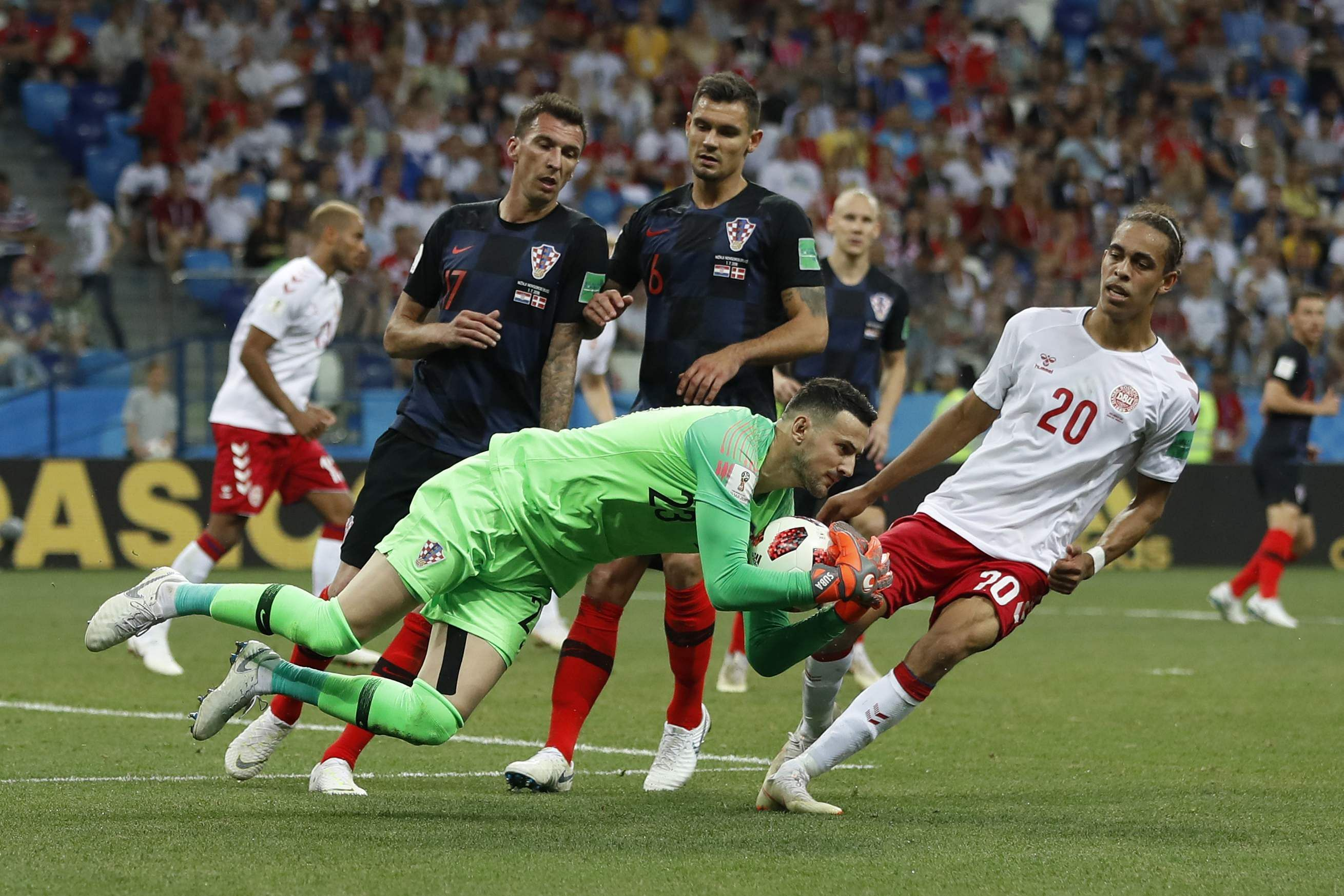 Croatia goalkeeper Danijel Subasic, front, secures the ball next to Denmark's Yussuf Yurary Poulsen, right, during the round of 16 match between Croatia and Denmark. (Photo | AP)