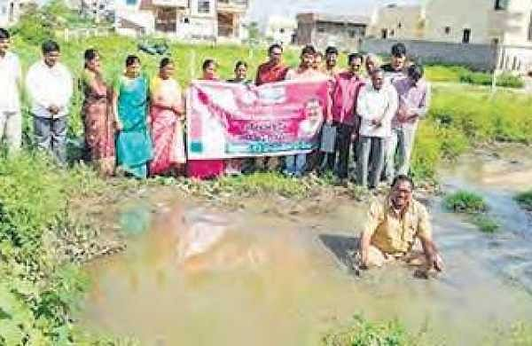Ruling TRS corporator from Hayathnagar S Tirumala Reddy staged a novel protest by entering into sewage water against inordinate delay in laying sewage lines in Hayathnagar, in Hyderabad on Friday   Express