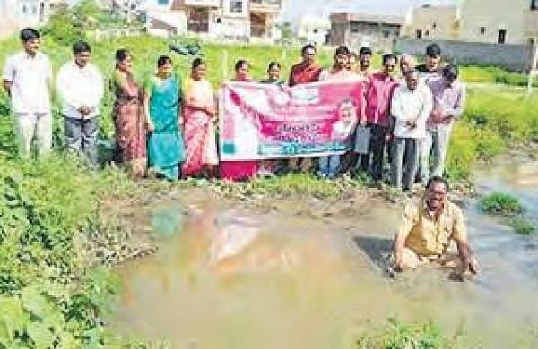 Ruling TRS corporator from Hayathnagar S Tirumala Reddy staged a novel protest by entering into sewage water against inordinate delay in laying sewage lines in Hayathnagar, in Hyderabad on Friday | Express