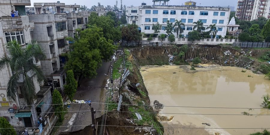 A road caves in after monsoon rainfall at Vasundhara in Ghaziabad. (Photo | PTI)
