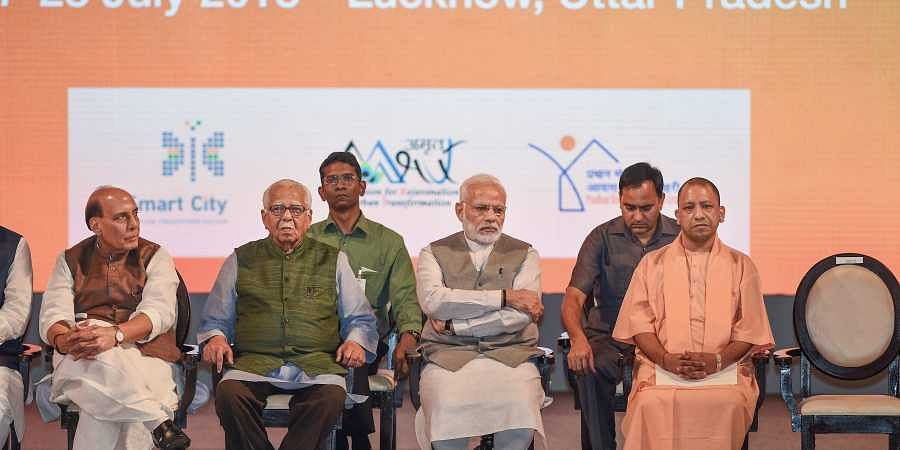 Prime Minister Narendra Modi with Uttar Pradesh Governor Ram Naik Chief Minister Yogi Adityanath and Union Home Minister Rajnath Singh during a programme to mark completion of three years of Smart City Mission AMRUT and Pradhan Mantri Avas Yojna in Luckno